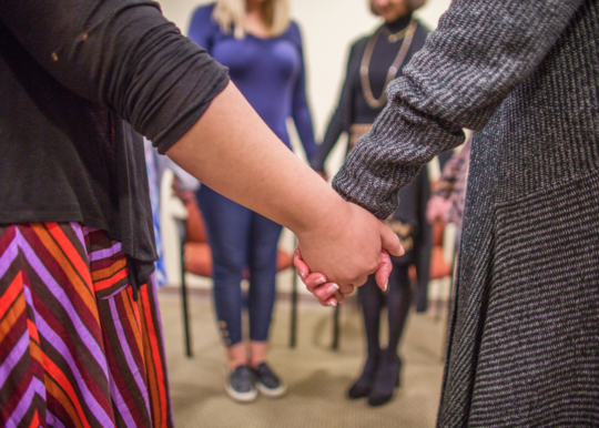 close up of two individuals holding hands in a group support session