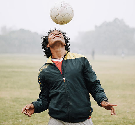 man bounces soccer ball on his head in a field