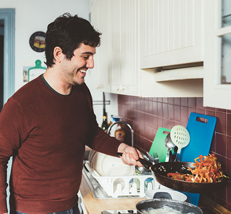 man with red sweater cooking food in a skillet while smiling