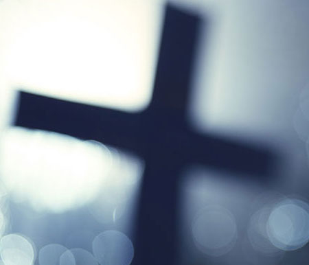 a blurred image of an illuminated cross with bokeh